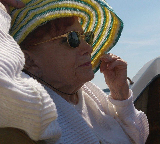 Old woman with orange hair, in a white sweater, with a sun hat