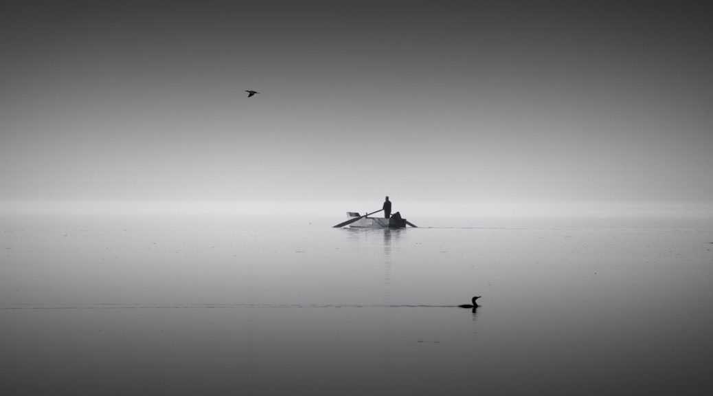 a white horizon, with water and sky meeting, in the middle a boat with a person on it